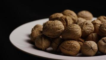 Cinematic, rotating shot of walnuts in their shells on a white surface - WALNUTS 083