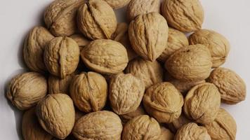 Cinematic, rotating shot of walnuts in their shells on a white surface - WALNUTS 044