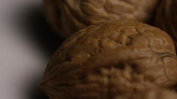 Cinematic, rotating shot of walnuts in their shells on a white surface - WALNUTS 024