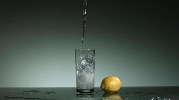 líquido transparente carbonatado que se vierte y salpica en cámara ultra lenta (1,500 fps) en un vaso lleno de hielo - líquido vertido 024