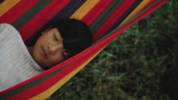 menina descansando deitada na rede ao ar livre em câmera lenta video