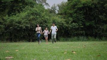 cámara lenta de padres con hija corriendo disfrutar en el parque