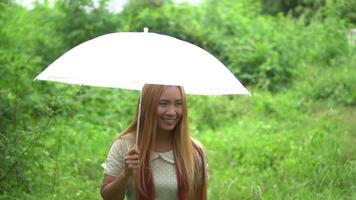 femme marche main tenant un parapluie blanc dans le parc video