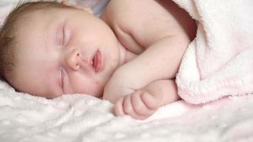 close-up do bebê recém-nascido menina está dormindo na cama, bons sonhos com o bebê, sono saudável.