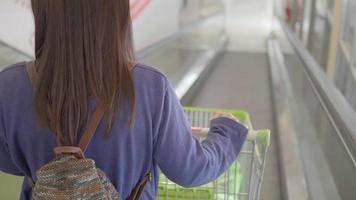 mulher asiática andando com um carrinho de mercado. video