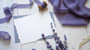 tarjeta en blanco blanca, sobre y cinta sobre un fondo de tela rosa y azul con flores de lavanda sobre un fondo blanco. video