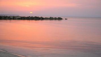 4k escénico amanecer rojo sol de fondo. video de cerca del sol naciente detrás del mar