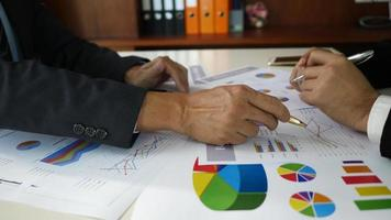 Businessman examining graphs with other coming people.