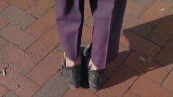 inclinação do pé até o quadril de uma mulher caminhando em uma calçada