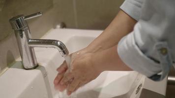 mulher lavando as mãos com água da torneira.