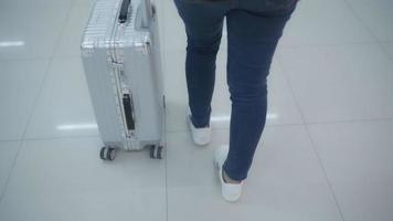 Zeitlupe - glückliche asiatische Frau, die Wagen oder Wagen mit viel Gepäck benutzt, das in der Terminalhalle geht.