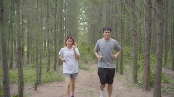 Healthy young athletic sporty Asian runner man and woman in sports clothing running and jogging on forest trail. video
