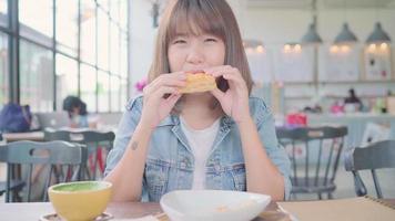 mulher asiática comendo pão e bebendo café enquanto está sentado em uma mesa em um café.