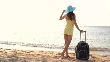 mulher na praia com uma mala video