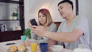 Atractiva pareja asiática joven distraída en la mesa con el periódico y el teléfono celular mientras desayuna.