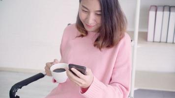 mulher asiática em roupa casual inteligente usando smartphone e bebendo café.