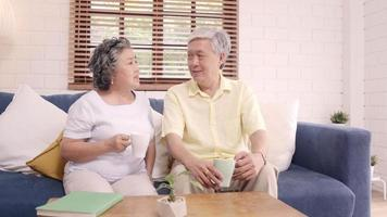 Asian elderly couple talking at home
