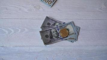 bitcoins dorados con billetes de un dólar