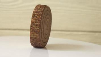 un soporte de madera gira contra una pared de madera blanca