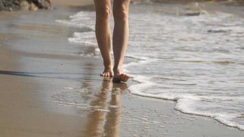 donna cammina sulla spiaggia