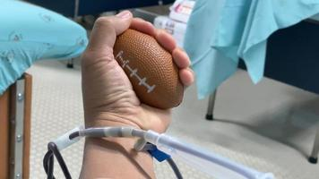 une personne serre une balle en donnant du sang
