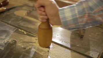 mão masculina segurando um macete de madeira
