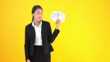 Mujer con mucho dinero en efectivo sobre fondo amarillo aislado