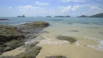 Beautiful rocky and sandy beach with clear water under cloudy blue sky.