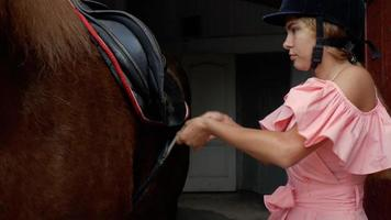 Horsewoman fastens the straps on the saddle