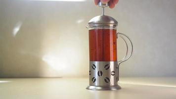 tetera de vidrio con té floreciente