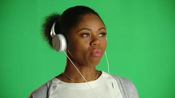 joven, mujer americana africana, goma de mascar, auriculares, 2 video