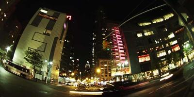 lasso di tempo di veicoli in transito sulla strada e edifici luminosi in 4K