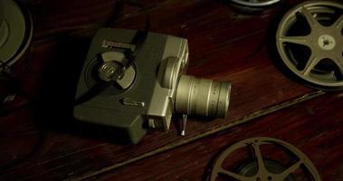 Toma panorámica corta de cuatro rollos de película, una lata y una cámara antigua sobre una mesa en 4k