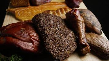 Rotating shot of a variety of delicious, premium smoked meats on a wooden cutting board - FOOD 060