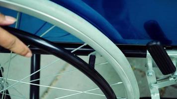 close-up da mão de um paciente segurando uma cadeira de rodas e dirigindo sozinho.