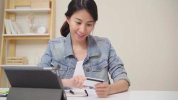 Mulher asiática usando tablet para fazer compras online com cartão de crédito video