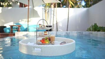 bandeja de desayuno flotando en una piscina