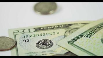 muitas moedas de um quarto de dólar caindo sobre duas moedas e duas notas de $ 20 na mesa branca, finalmente quatro moedas e ambas as notas colocadas na cena em 4k