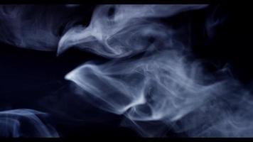 fumaça suave movendo-se lentamente desenhando linhas finas e ondas em fundo escuro em 4k