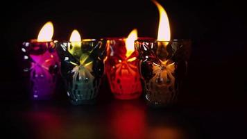 velas en contenedores de calaveras de colores