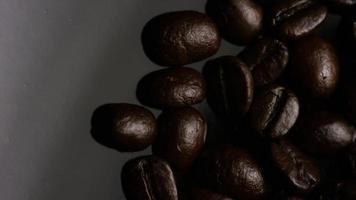 dose rotativa de deliciosos grãos de café torrados em uma superfície branca - grãos de café 008