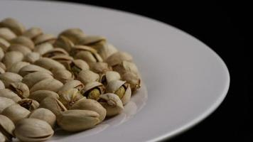 Cinematic, rotating shot of pistachios on a white surface - PISTACHIOS 021