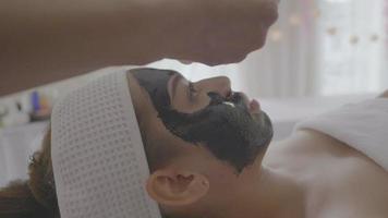 bela jovem recebe terapia de spa com carvão video