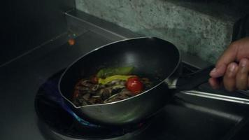 Slow motion - Chefs is preparing and cooking food at the kitchen of a restaurant.