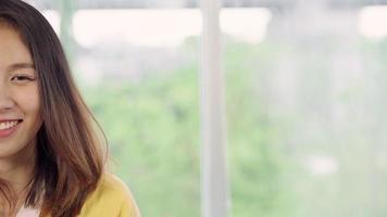 adolescente mujer asiática que se siente feliz sonriendo y mirando a la cámara mientras se relaja en su sala de estar en casa.