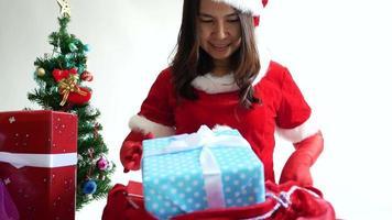 mujer vestida como la sra. claus preparando una bolsa de regalo para navidad.