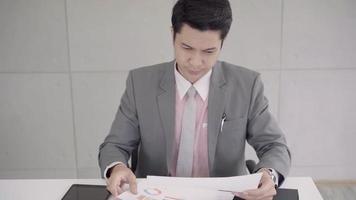 câmera lenta - empresário chateado na mesa no escritório. empresário asiático sendo deprimido por vir ao cargo. Yong homem de negócios a pensar e não trabalhar com estresse fingindo colocar a mão na cabeça. video