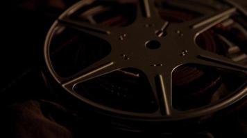 Cerca de dos rollos de película girando con iluminación oscura en 4k