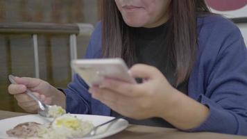mulher asiática usando smartphone e comendo.