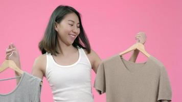 jovem bonita elegante mulher asiática escolhendo roupas em roupas casuais. video